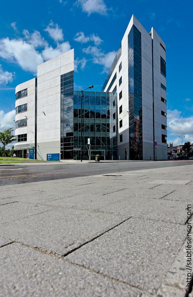 Photograph of conremporary University building against blue sky with pavement.