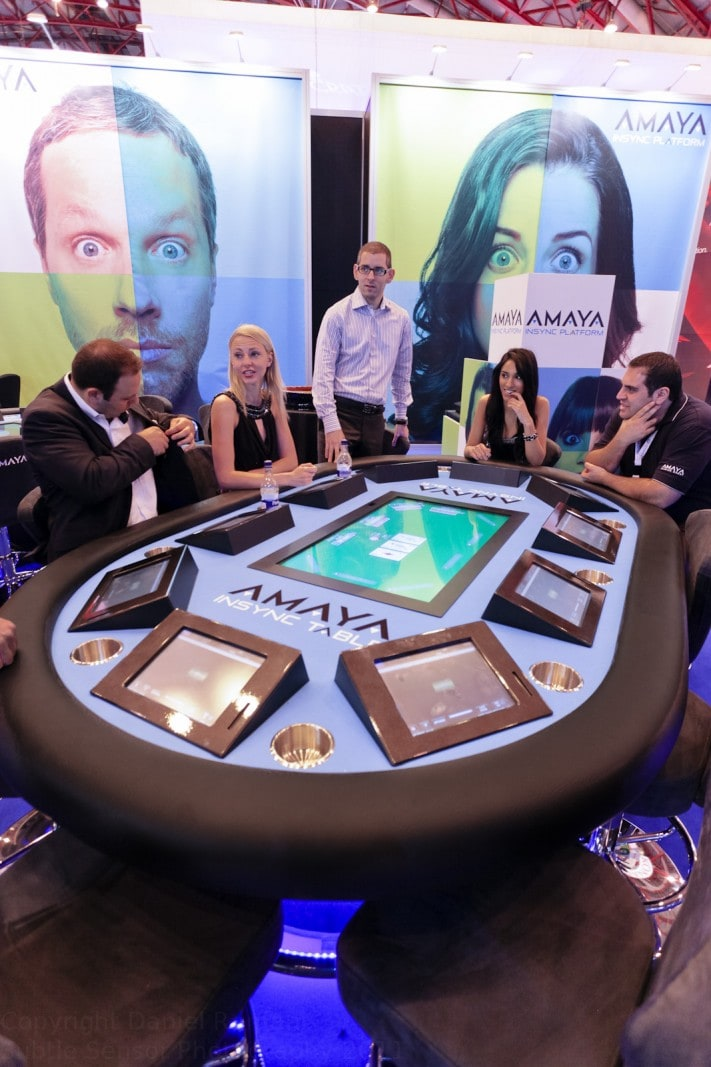 Photograph of delagates networking at AMAYA's stand in London Exhibition