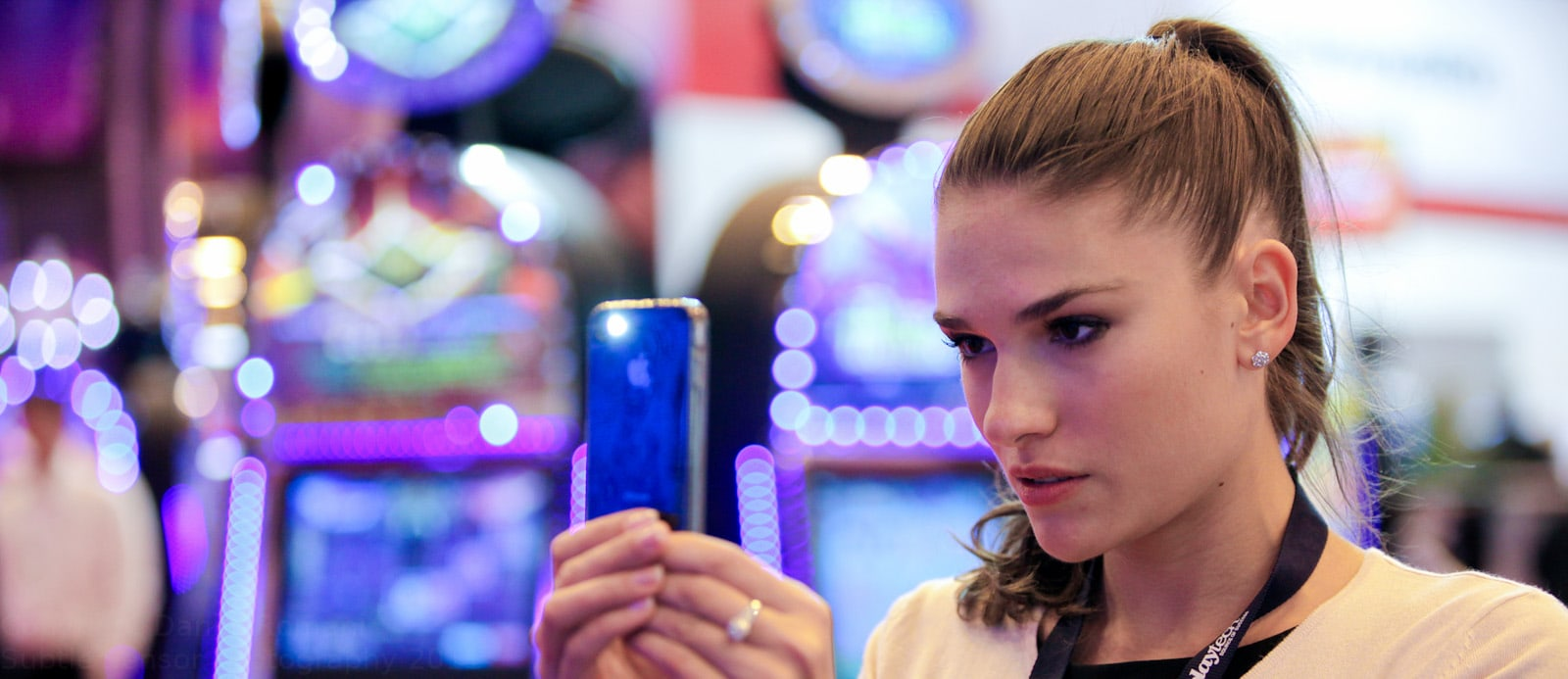 Photograph of a girl using an iPhone camera with neon lights in background