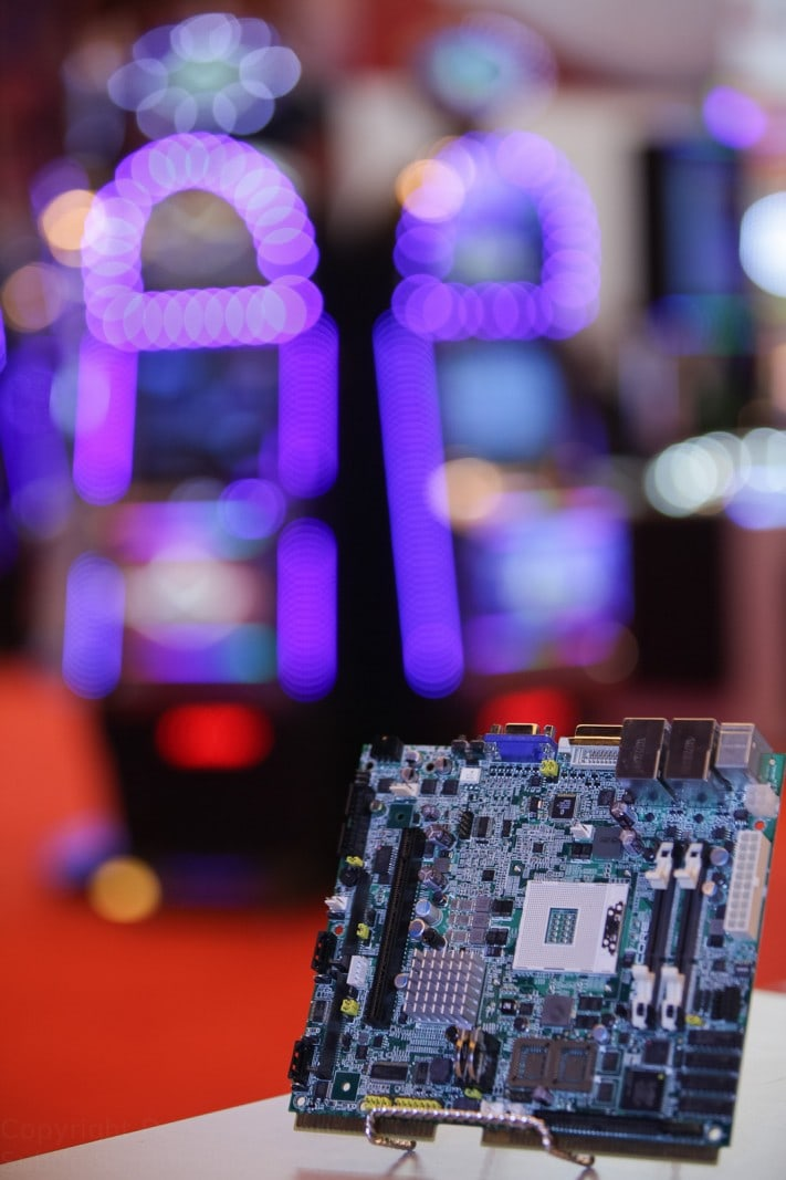 Photograph of a circuit board with fruit machines blurred in background