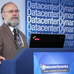 Photograph of speaker at Datacenter Dynamics conference with logo in background