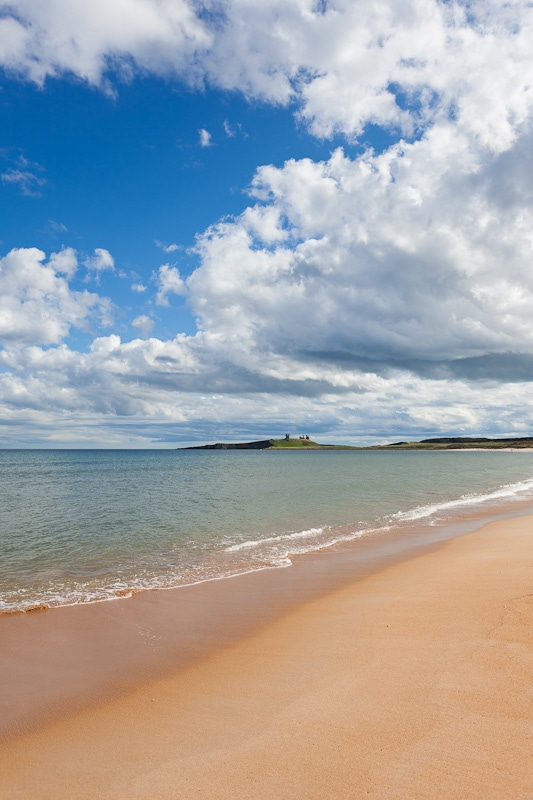 Photograph of Dunstanburgh Castle under big blue skies with white cumulous clouds and Embelton Bay's turquoise water in front.