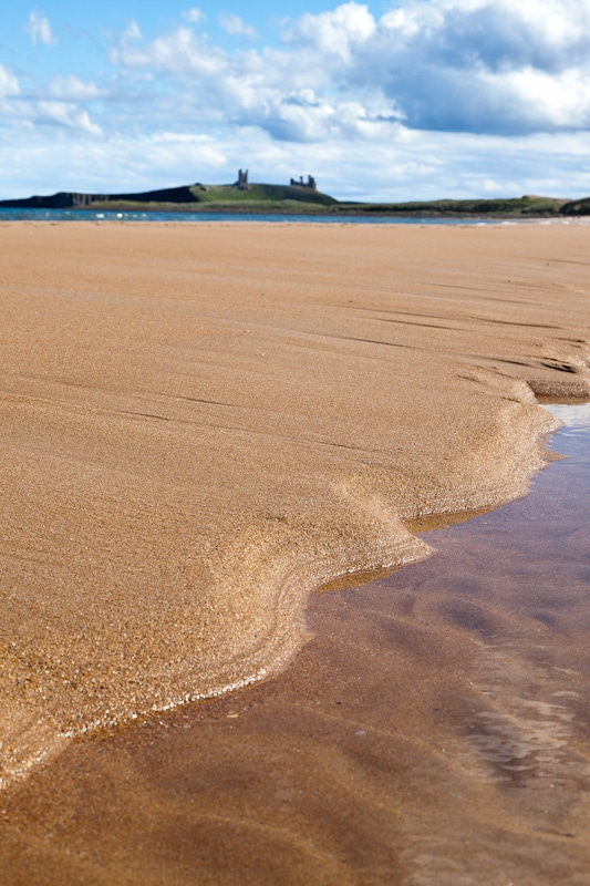 Photograph of smooth sands on Embelton Bay with Dunstanburgh Castle appearing over the horizon.
