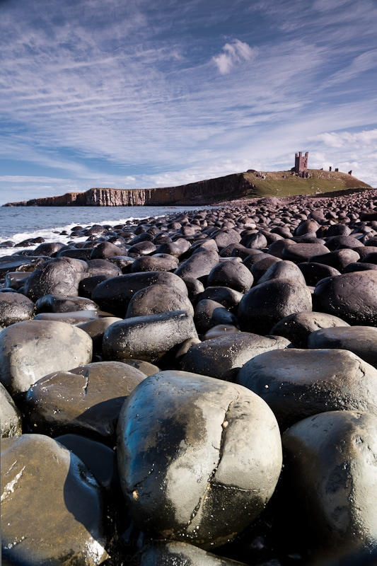 Photograph of Dunstanburgh Castle against a dramatic cirrus sky with the distinctive big black boulders in the foreground.
