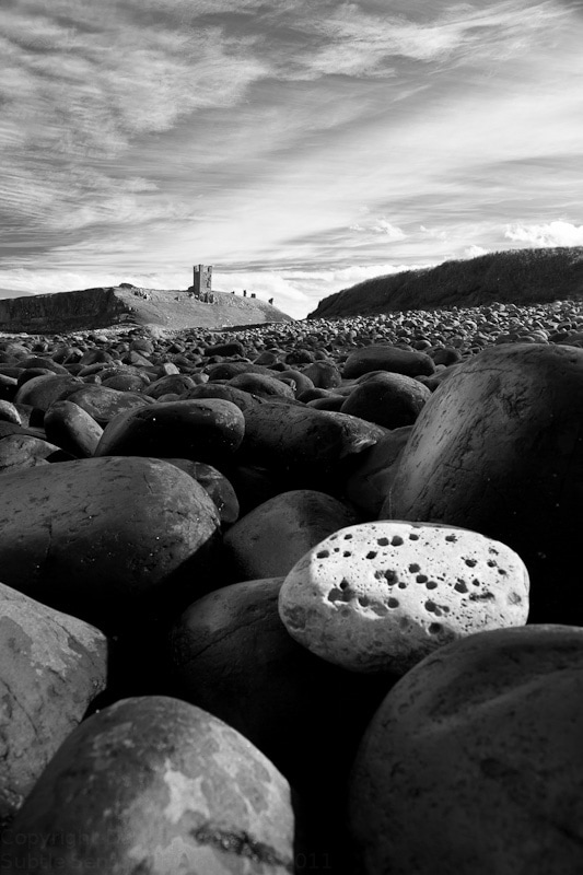 Black & White photograph of the black boulders of Embleton Bay with Dunstanburgh Castle in the background and a white, cratered stoone in the foregound, like a fallen moon.