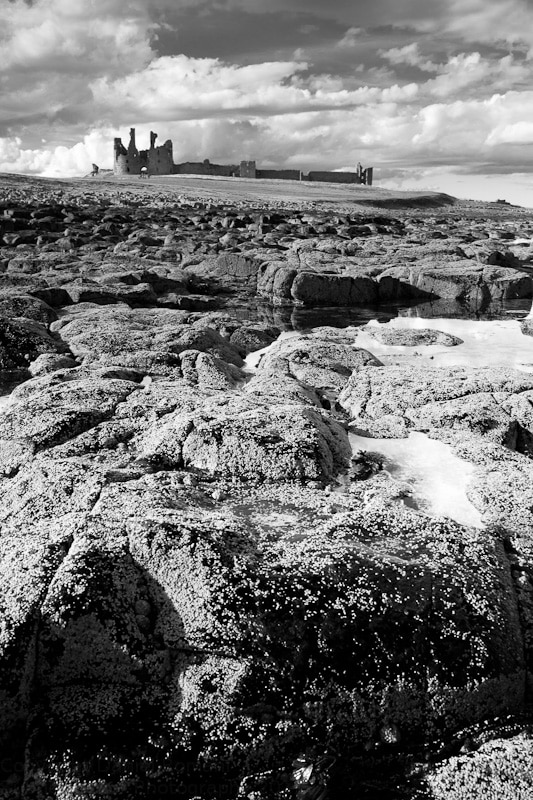 Black & White photograph of rocky foreground with ruins of Dunstanburgh Castle set against a cloudy sky in the background.