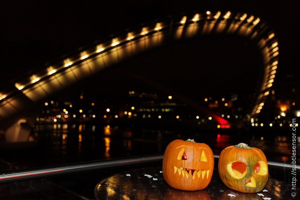 Halloween carved pumpkins with Millennium Eye bridge in background