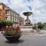Small fountain in an Italian village square with cobbled foreground.