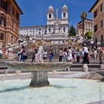 A fountain takes up the foreground as tourists climb the Spanish Steppes on a sunny day in Rome, Italy