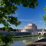 Castel Sant'Angelo seen through summer boughs across the river Tiber
