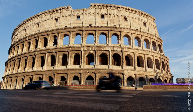 A worms eye view of traffic speeding past the Colesseum, Rome, Italy.