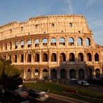 The setting sun bathes the Colosseum in a warm golden light.