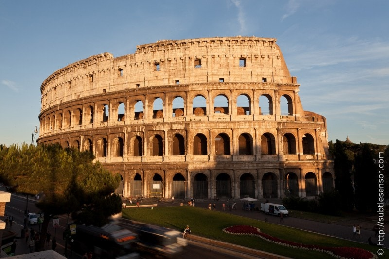 The setting sun bathes the Colosseum in a warm golden light